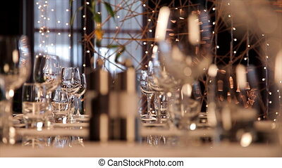 Restaurant table set ready for dinner party. Bokeh lights on...