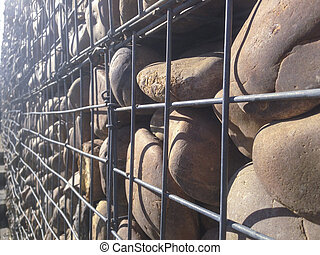 Wall protected with river pebble stones in iron mesh. This...