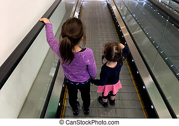 Two sister holds hands on moving walkway. Real people. copy...