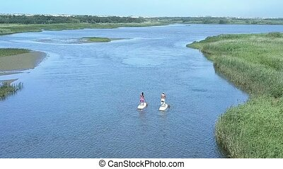 Man and woman stand up paddleboarding - Aerial view of man...