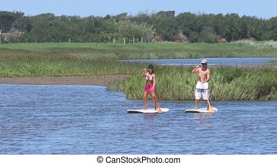 Man and woman stand up paddleboarding on lake. Young couple...