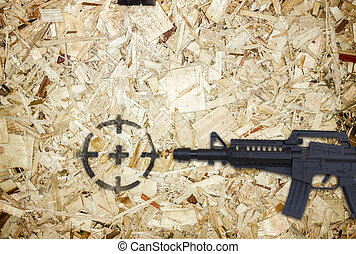 gun and target on wooden background.