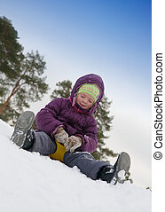 child sliding in the snow - The boy goes for a drive on an...
