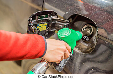 Refilling the car with fuel - Hand refilling the car with...