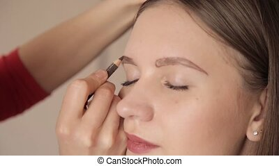 make-up artist drawing eyebrows of client by pencil. Close...