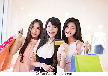 happy woman group holding shopping bags and  credit card at  mall