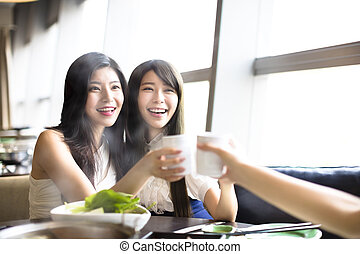 happy Group of girl friends toasting and eating in the...