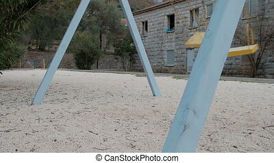 Empty playground with moving swig in winter in Europe. Blue...