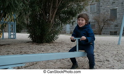 Small boy riding seesaw in playground in winter. Nobody else.