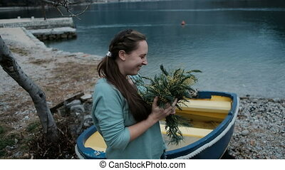 Adult Caucasian woman is happy receive bouquet of mimosa near lake.