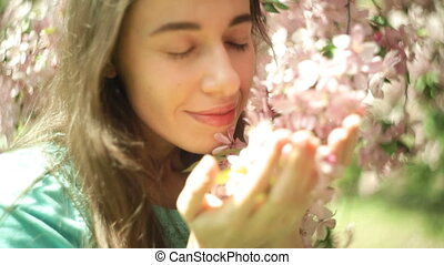Beautiful woman sniffing flowers in the spring garden.