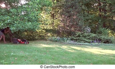 Woman working in garden cutting grass with lawn mower. 4K -...