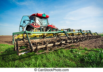 Farmer in tractor preparing land with seedbed cultivator in...