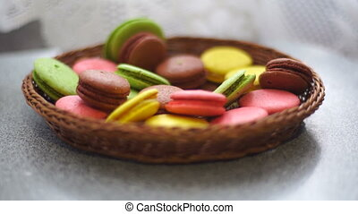 colored macaroon cookies falls in the wicker plate on a...