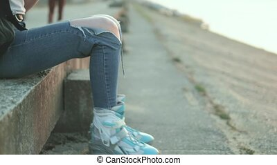 Beautiful woman listening to music in roller skates on the...
