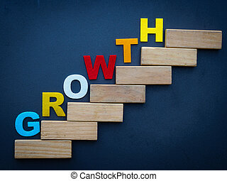 "Wood block stacking as step stair with colorful of ""GROWTH"" word"