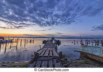 exciting long exposure landscape on a lake with wooden pier and boats