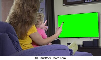Young mother with her child girl watch tv and show finger. Green chroma screen