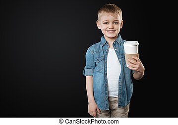 Positive delighted little kid holding paper cup from coffee...