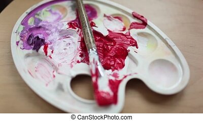 Smeared with the brush in the palette with paints. Red and...