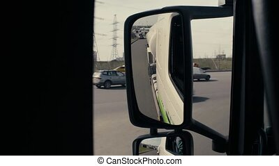 View in tank car's rearview mirror on highway