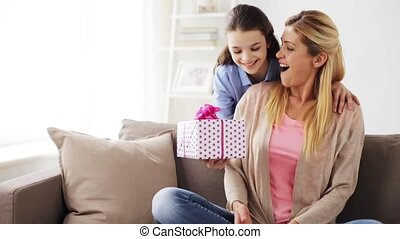happy girl giving present to mother at home - people,...