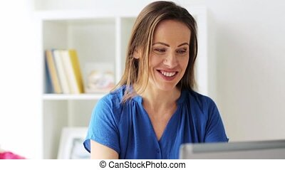 happy woman with laptop working at home or office -...