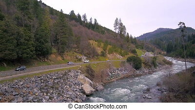 Asphalt winding road going along the mountain river,...