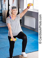 Positive well built woman holding dumbbells