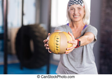 Sports ball being held by a nice elderly woman