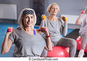 Happy active woman building up her muscles