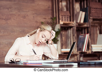 Young tired businesswoman using laptop and taking notes