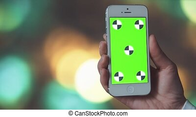 Smartphone with Green Screen on before Bokeh Background -...