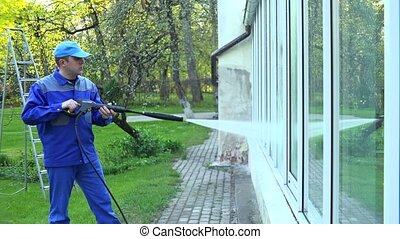 man wash glass windows with water pressure jet. Building...