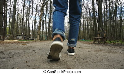girl goes through the Woods. Close up of female feet
