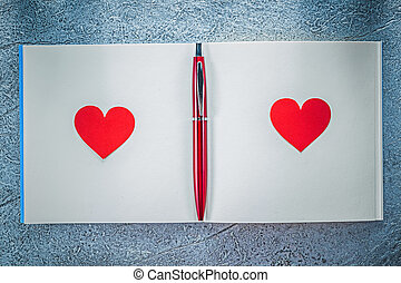 Red hearts biro pen clean notepad on metallic background...