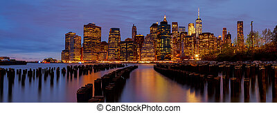 New York City Manhattan skyline with skyscrapers over Hudson River illuminated lights at dusk after sunset.