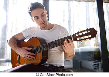 plyaying the guitar - Young man trying to produce new melody...