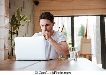 man siyying near laptop - Yong brunette man sitting and...