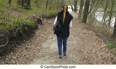 girl descends along the trail to the Lake through the forest