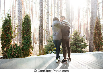 couple standing on doorstep - Backview of hugging young man...