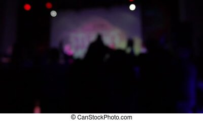 A crowd of people dancing at a rock concert in slow motion. blurred image. Out of focus.