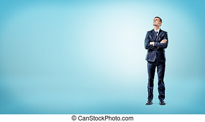 A businessman on blue background standing with hands crossed...