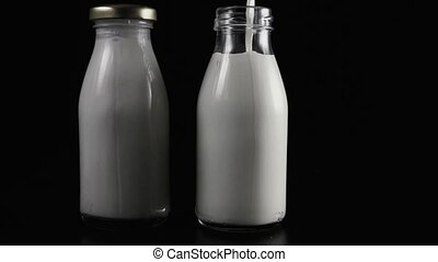Two milk bottles on a black background. Slow motion
