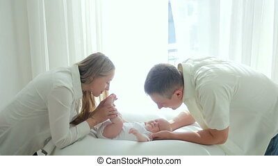 parents mother and father kiss newborn son lying