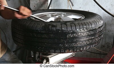 Mechanical repairs a tire in the garage on a indoor tire...
