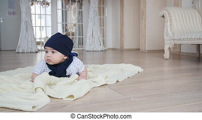 Cute baby boy lying down on carpet on floor
