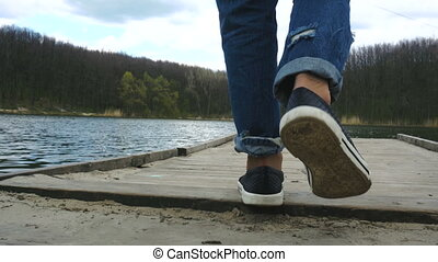 girl in the sneakers walks the pier - young girl in the...