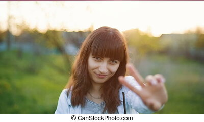 Woman Showing a Peace Sign at Sunset - Smiling woman showing...