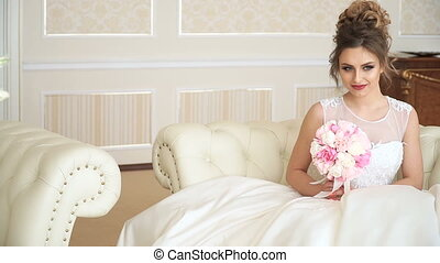 An attractive young woman bride with a bouquet of flowers is sitting on the couch in a luxurious room. She is waiting for someone with excitement
